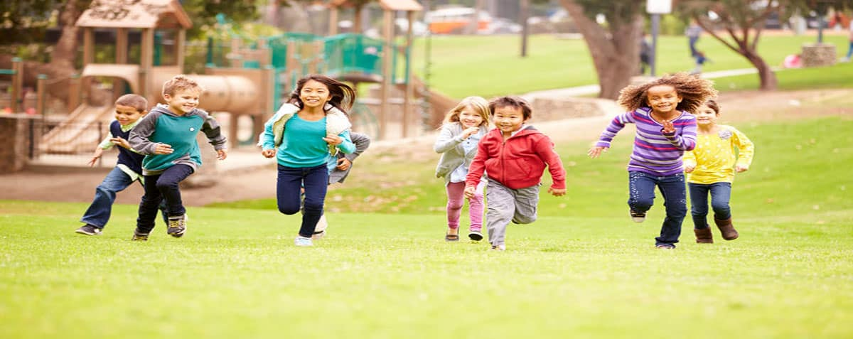 Group of Young Children Running in the Park